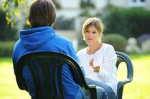 Bild Gespräch zwischen Schüler und Lehrkraft im Garten